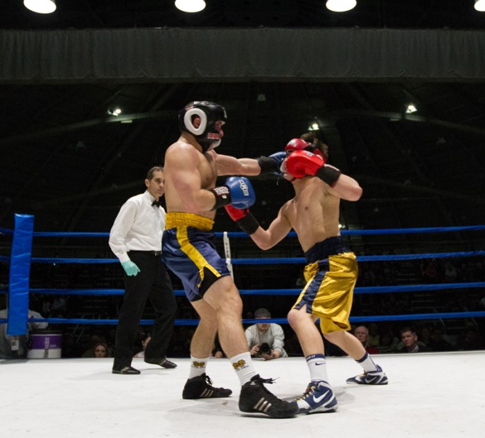 Senior captain Chris Hinman, left, connects on a jab to the face of freshman Garrett Schmelling in the semifinal round Tuesday night.