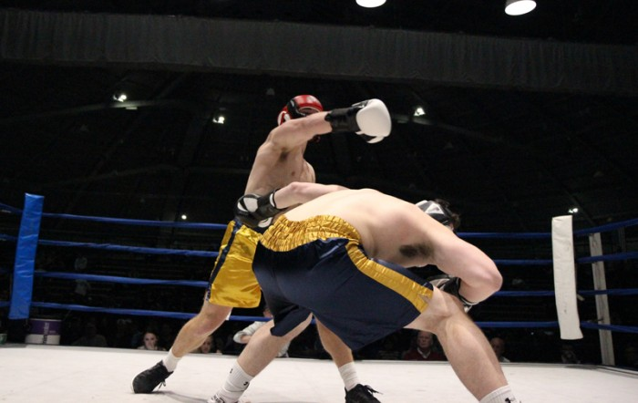 Senior captain Ricky Neville, right, prepares for a hook from senior Michael Smoljan in the semifinal round Tuesday night. Neville was victorious by split decision and will fight junior Evan Escobedo in the finals Sunday for a chance at his first championship after falling in last year's title bout.