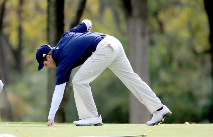 Irish senior Andrew Carreon retrieves his putt during the Fighting Irish Gridiron Golf Classic on Oct. 9, 2013.