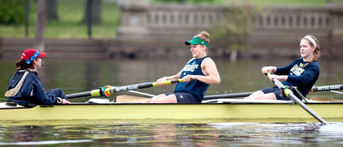 Senior Molly Bruggeman and junior Erin Boxberger sroke down the river as senior coxswain Christina Dines leads the crew in practice on April 25.