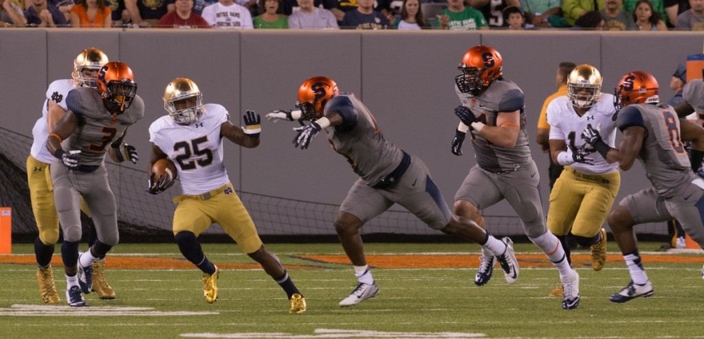 Irish sophomore running back Tarean Folston attempts to break away from a trio of Syracuse defenders during Notre Dame's 31-15 win Saturday night over the Orange.