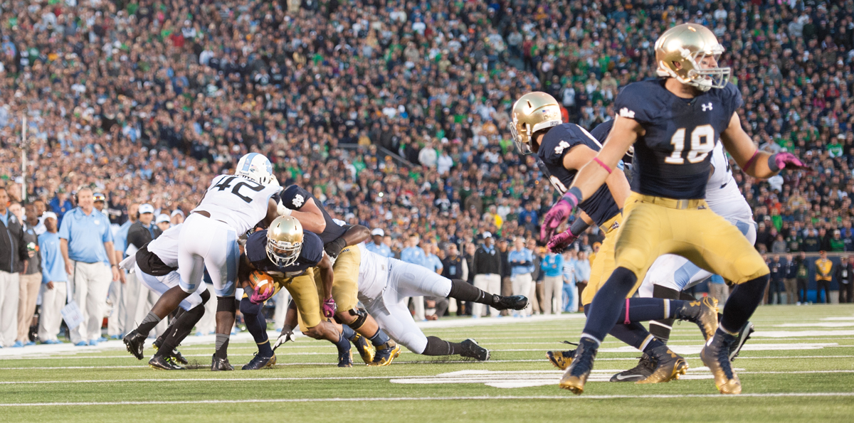 Irish sophomore running back Tarean Folston tries to squirt free from a pack of North Carolina defenders during Notre Dame's 50-43 victory over the Tar Heels on Saturday at Notre Dame Stadium. Folston did the heavy lifting for the Irish in the second half and notched two fourth-quarter scores.