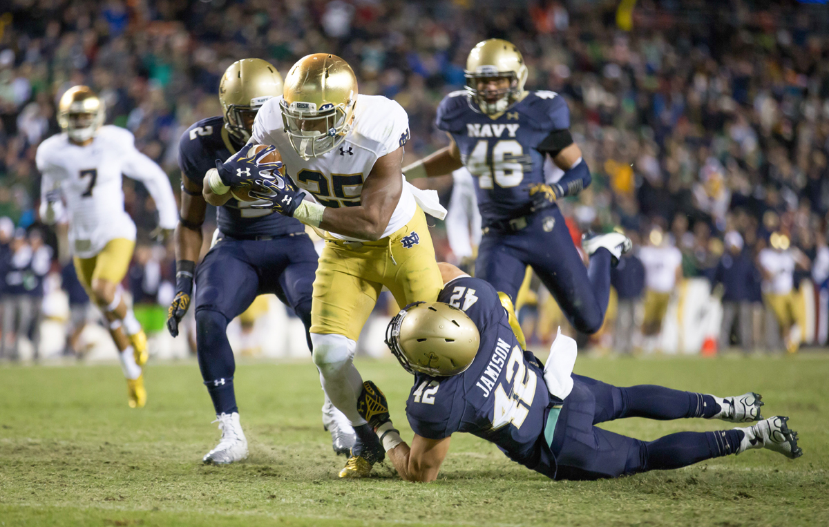 Irish sophomore running back Tarean Folston tries to shimmy free from Navy defenders Saturday.