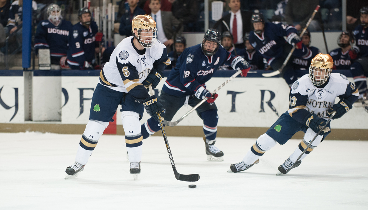 Irish junior defenseman Andy Ryan (left) pushes the puck up the ice in Notre Dame's 3-3 tie with Connecticut on Friday.