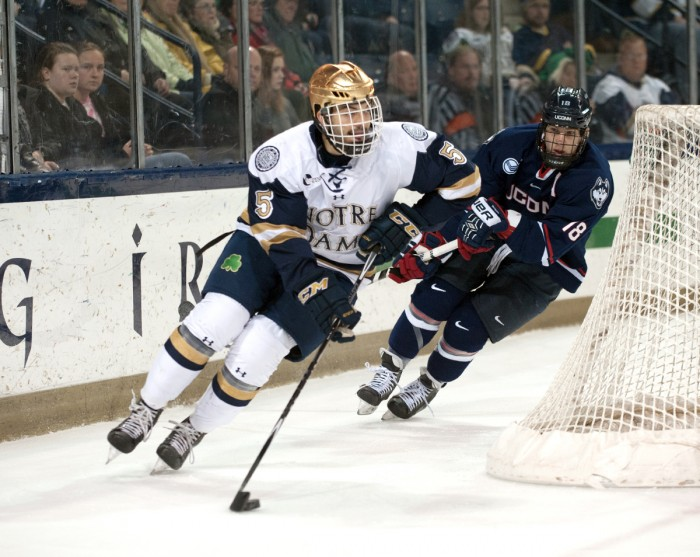 Irish senior defenseman Robbie Russo circles the net Jan. 16 against UConn at Compton Family Ice Arena. The two teams tied, 3-3.