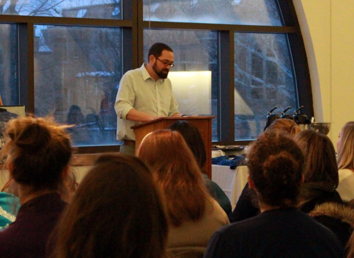"Aaron Bremyer, head of the English writing center at Saint Mary's, reads a poem by a student during the ""Then and Now"" poetry reading."