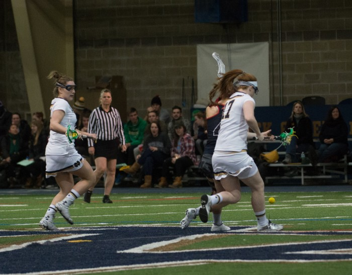 Irish senior defender Barbara Sullivan, right, chases after a ground ball during Notre Dame's 17-5 win over Detroit on Sunday at Loftus Sports Center. Sullivan is this year's team captain.