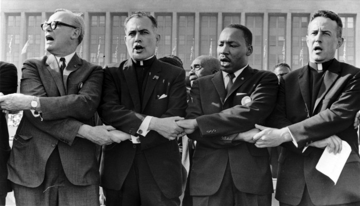 """Fr. Hesburgh, second from left, links arms with Dr. Martin Luther King, Jr., to his right, and sings """"We Shall Overcome"""" during a 1964 civil rights rally at Chicago's Soldier field."""