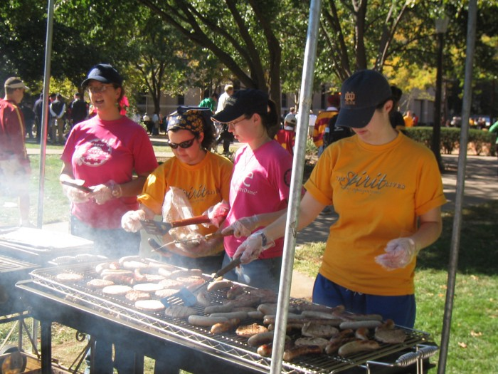 Members of the Society of Women Engineers grill hot dogs and hamburgers before a Notre Dame football game as part of its fundraising efforts.