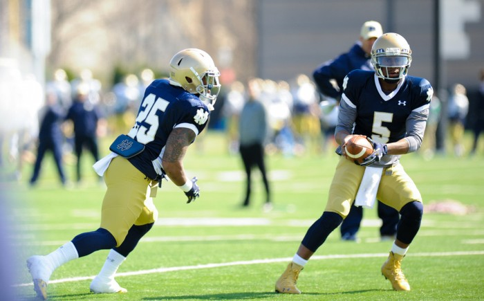 Irish graduate student quarterback Everett Golson prepares to hand the ball off to junior running back Tarean Folston during Saturday's practice at Labar Practice Complex.