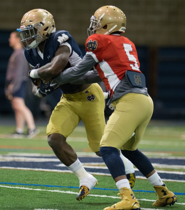 Irish graduate student quarterback Everett Golson hands the ball off to junior running back Greg Bryant during a March 27 practice.