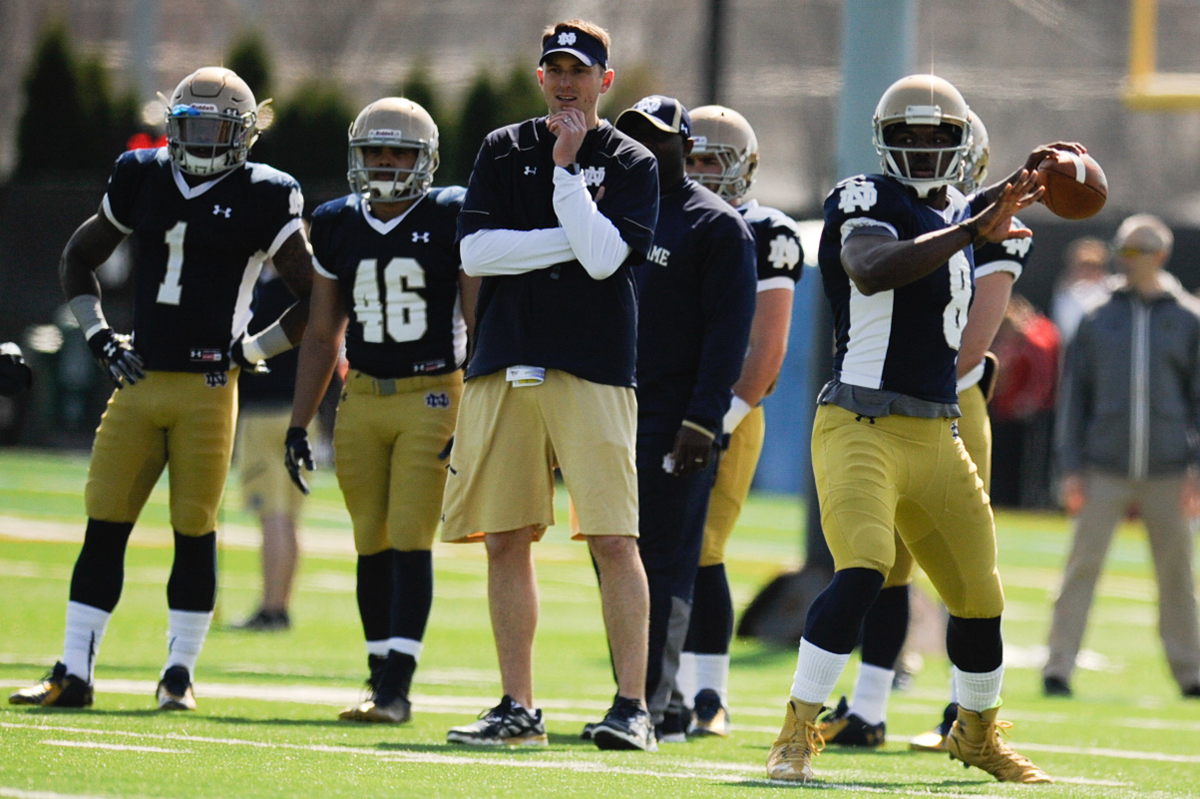 Irish offensive coordinator and quarterbacks coach Mike Sanford watches as junior quarterback Malik Zaire winds up for a pass during Notre Dame's practice last Saturday at LaBar Practice Complex.