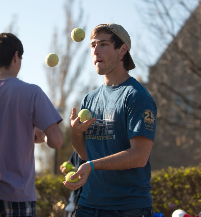 A member of the Notre Dame juggling club develops his juggling skills with tennis balls.