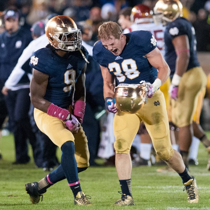 Junior linebacker Jaylon Smith, left, and graduate student linebacker Joe Schmidt celebrate during a 14-10 win over USC on Oct. 19, 2013.