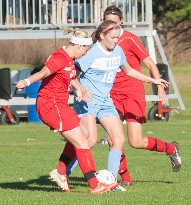 Senior midfielder Maggie McLaughlin dribbles between two defenders in a 2-0 loss against Olivet on Oct. 28 at Angela Athletic Facility.
