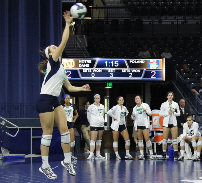 Junior captain middle blocker Katie Higgins jumps for a serve during an exhibition match against Polish club team Dobrowa.