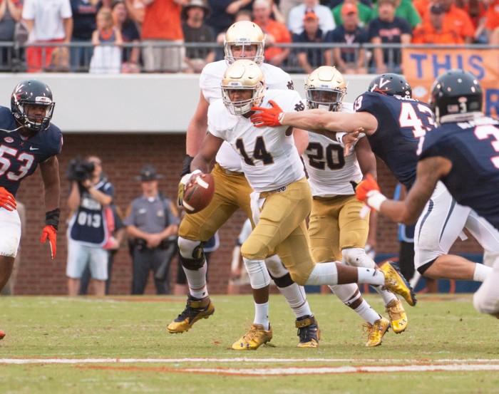 Irish sophomore quarterback DeShone Kizer evades a tackle during Saturday's 34-27 win over Virginia at Scott Stadium.