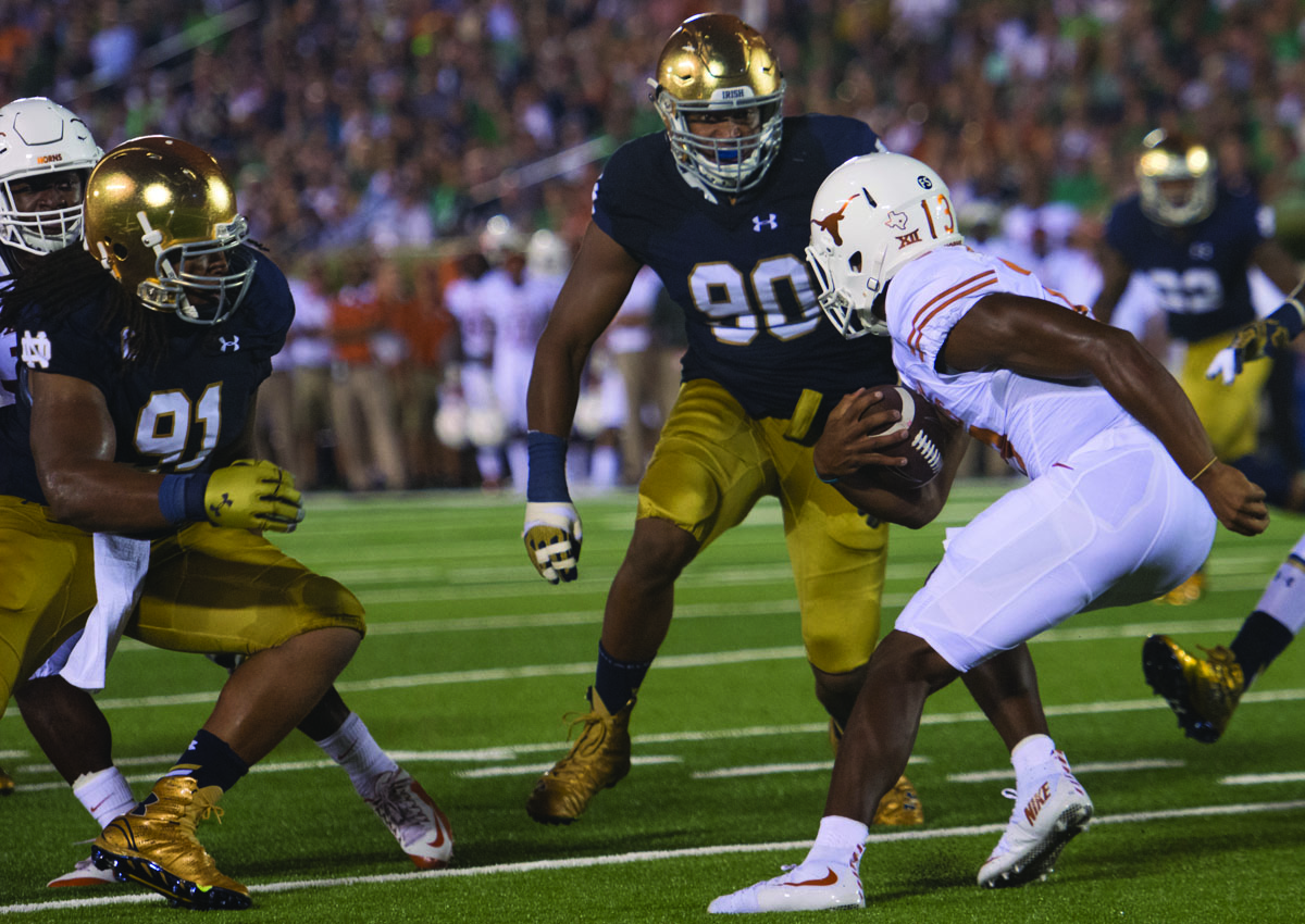 Irish senior defensive lineman Sheldon Day, left, and junior defensive lineman Isaac Rochell pursue Texas redshirt freshman quarterback Jerrod Heard during Notre Dame's 38-3 victory over the Longhorns.