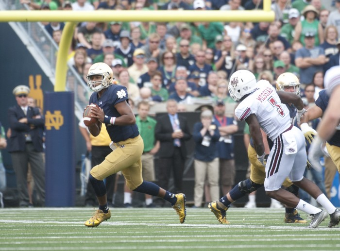 Irish freshman quarterback Brandon Wimbush rolls out to pass during his Notre Dame debut Saturday. Wimbush ran for a touchdown, the first in his Irish career, and had a deep pass to junior receiver Will Fuller, his first attempt, ruled incomplete after a video review. Wimbush also had a would-be touchdown pass called back due to an Irish penalty.