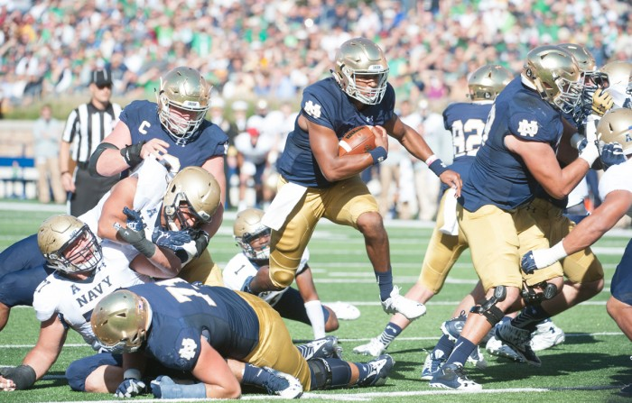 Irish sophomore quarterback DeShone Kizer slips through a sea of chaos during Notre Dame's 41-24 victory over Navy. Kizer was tackled at the 1-yard line, but the Irish scored on the next play. Kizer went 22-of-30 with 281 yards and one touchdown through the air to go along with another touchdown on the ground in the win.