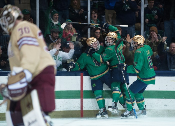 Sophomore defenseman, left green jersey, celebrates a goal with teammates