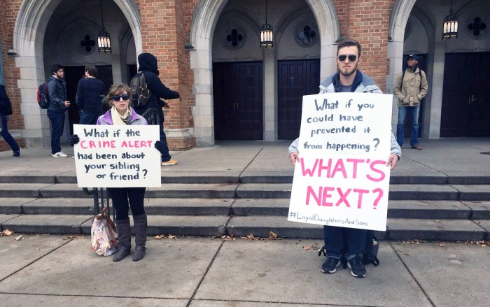 """Seniors Tess Rinaldo, left, and Skyler Hughes hold signs outside of South Dining Hall to raise awareness for sexual assault and rape culture as part of Loyal Daughters and Sons' """"Talk About it Tuesday"""" campaign."""