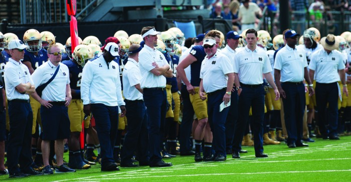 Members of the Irish coaching staff stand on the sidelines during the Blue-Gold Game on April 18. Notre Dame's new position coaches have found success in their first year despite injuries to starters.