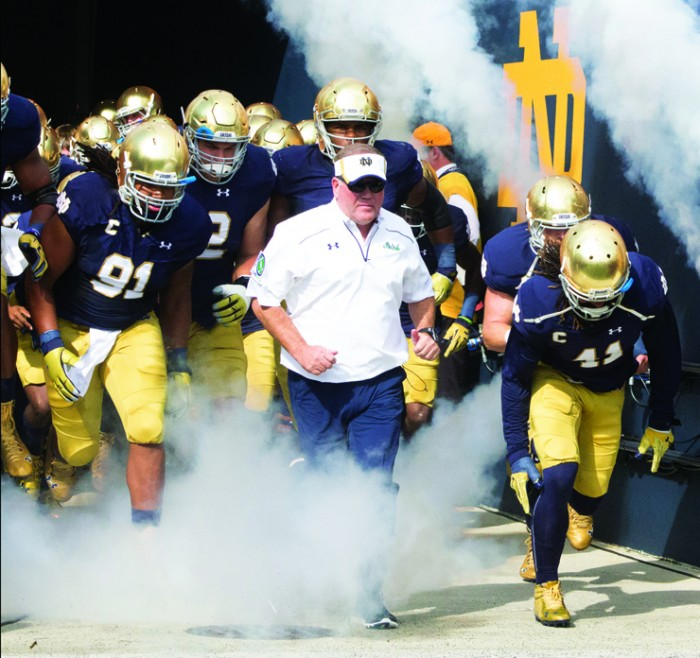 Irish head coach Brian Kelly leads his team onto the field before Notre Dame's 62-27 win against Massachusetts on Sept. 26. Kelly is a perfect 5-0 so far in Shamrock Series games.