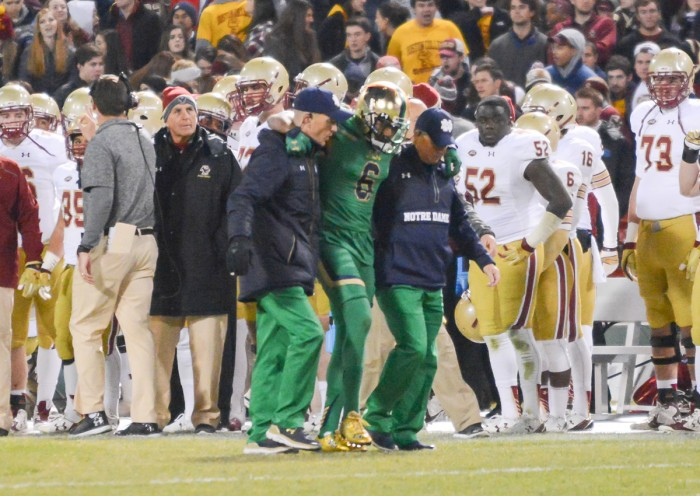 Senior cornerback KeiVarae Russell is helped off the field during Notre Dame's 19-16 victory over Boston College on Saturday. Russell was diagnosed with a broken tibia and is out for six to eight weeks.