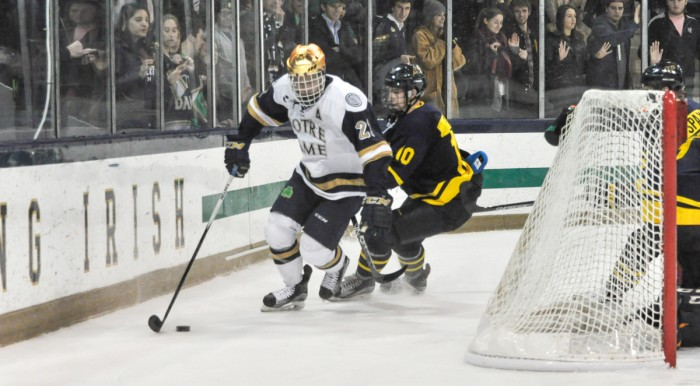 Irish senior left wing Mario Lucia fends off a Merrimack player during Notre Dame's 7-2 win Friday at Compton Family Ice Arena.