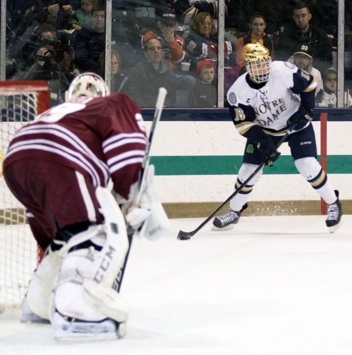 Sophomore center Jake Evans looks to pass the puck during Notre Dame's 5-1 victory over UMass at Compton Family Ice Arena.