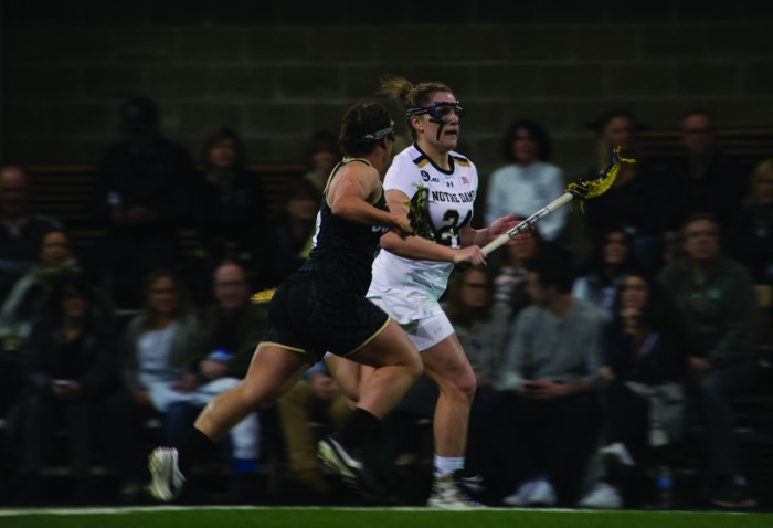 Irish junior midfielder Casey Pearsall carries the ball down the field during Notre Dame's 14-4 win over Colorado on Friday at Loftus Sports Center. Pearsall had a goal and two assists in the Irish victory.