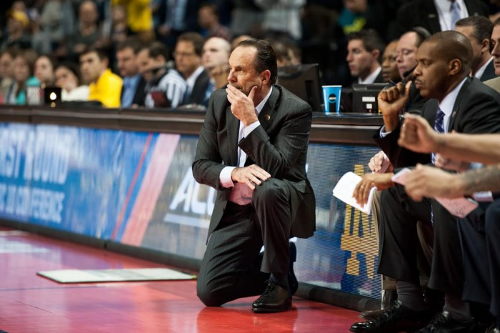 Irish head coach Mike Brey kneels on the sideline during Notre Dame's 70-63 win over Michigan on Friday in Brooklyn, New York.