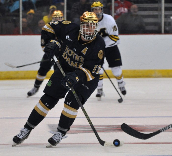 Irish senior left wing Sam Herr carries the puck up the ice during Notre Dame's 3-2 loss in overtime against Michigan on Saturday at U.S. Bank Arena.