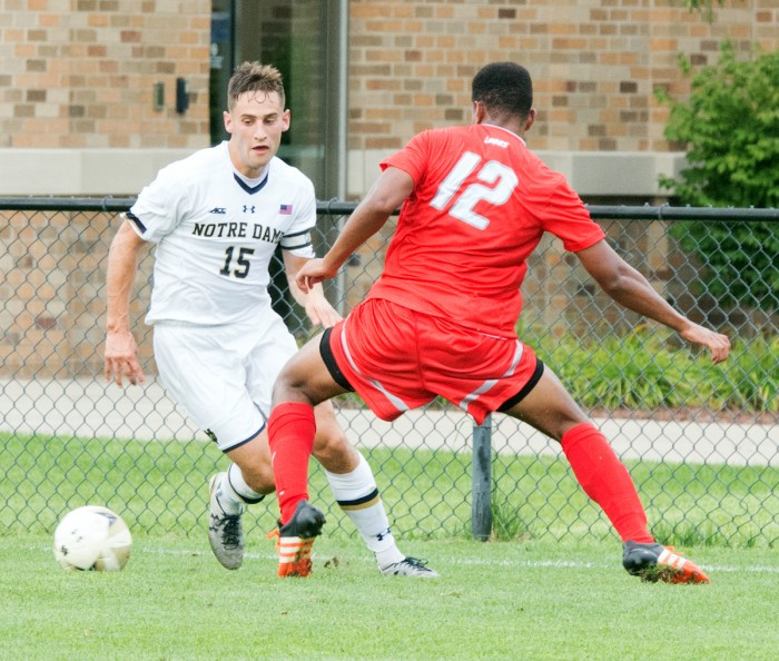 Irish graduate student midfielder Evan Panken attempts to dribble the ball around a defender during Notre Dame's 1-0 victory over New Mexico on Aug. 28 at Alumni Stadium.