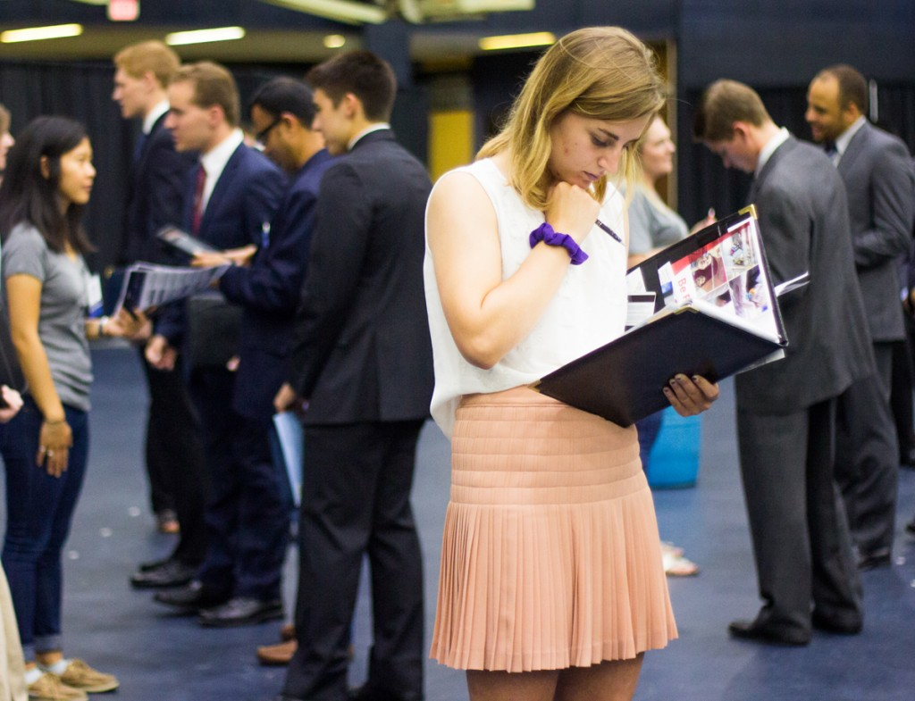 A student reviews informational brochures provided by visiting companies at the Fall Career Expo. The Expo, held in the Joyce Fieldhouse, allowed students to meet and interact with prospective employers.
