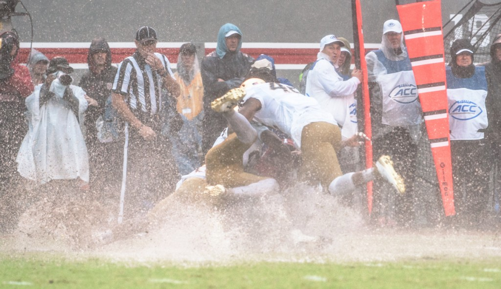 Irish freshman defensive lineman Julian Okwara, top, joins freshman cornerback Julian Love, middle with cleats up, and sophomore running back Dexter Williams in tackling the N.C. State kick returner Saturday in the Irish loss. This was a common sight throughout the day as players landed in puddles or slid for five yards after falling or diving.