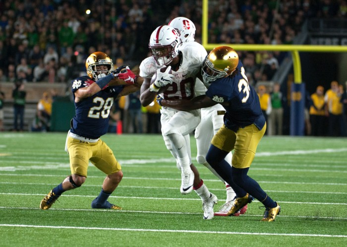 Sophomore saftey Nicco Fertitta, left, and senior cornerback Cole Luke make a tackle on a Stanford ball carrier in Saturday's 17-10 loss to the Cardinal.