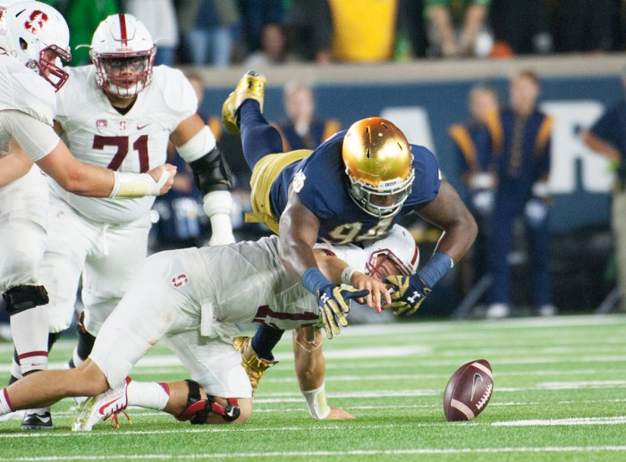 Irish graduate student defensive lineman Jarron Jones dives over Cardinal senior quarterback Ryan Burns to recover a fumble during Notre Dame's 17-10 loss to Stanford at Notre Dame Stadium on Oct. 15.