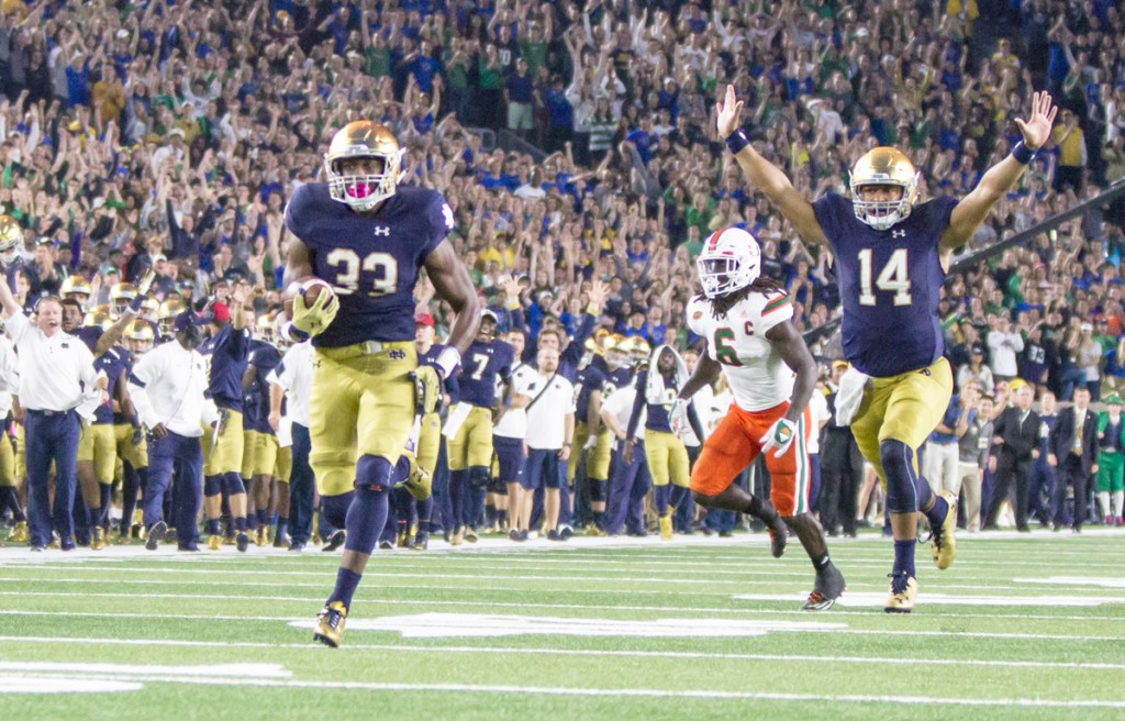 Irish sophomore running back Josh Adams sprints into the end zone to score the game-tying touchdown against Miami on Saturday at Notre Dame Stadium as junior quarterback DeShone Kizer, right, begins celebrating with the rest of the Irish faithful. Sophomore kicker Justin Yoon hit a 27-yard field goal with 30 seconds left to give the Irish the 30-27 win.