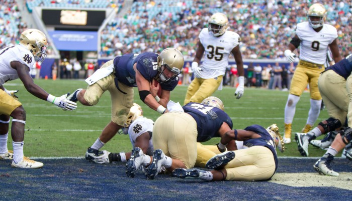Navy senior quarterback Will Worth dives into the end zone during Notre Dame's 28-27 loss to the Midshipmen on Saturday in Jacksonville. Worth ran for 175 yards and two touchdowns in the Navy win.