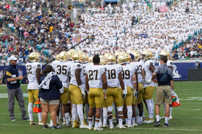 Notre Dame meets in a huddle during 4th quarter. The midshipmen stand cheering in their formal uniforms in the background.