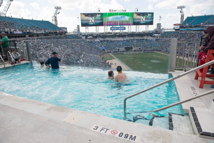 Fans overlook Everbank Field in pool inside stadium. A plexiglass side allows for watching the game even while underwater.
