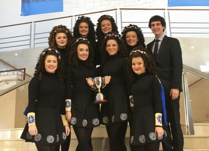The eight ceili dancers on the Notre Dame/Saint Mary's Irish Dance Team and their student coach, Robert Black, hold their championship trophy.