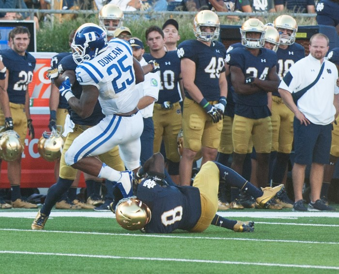 Irish sixth-year graduate student Avery Sebastian, on the ground, helps tackle a Duke player during Notre Dame's loss Sept. 24.