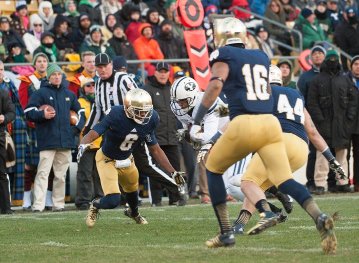 "Senior cornerback KeiVarae Russell, left, prepares to make a tackle during Notre Dame's 23-13 win over BYU at Notre Dame Stadium on Nov. 23, 2013. Russell was one of five players suspended in summer 2014 as part of the ""Frozen Five"" scandal. Notre Dame was placed on probation by the NCAA and ordered to vacate wins from the 2012 and 2013 seasons Tuesday."