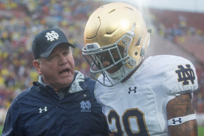 Brian Kelly talks to freshman receiver Kevin Stepherson during halftime.