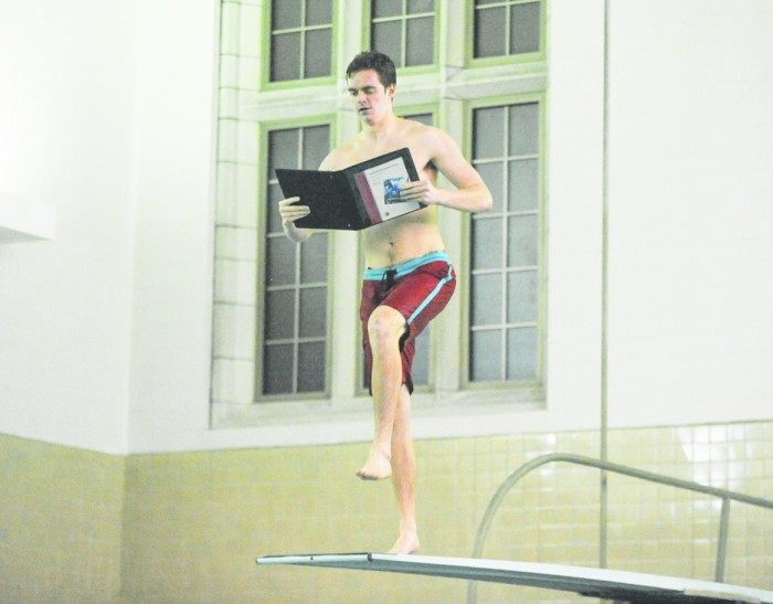 Sophomore Jack Waltrich prepares to jump off a Rockne Memorial diving board while pretending to study as part of the dorm's event.