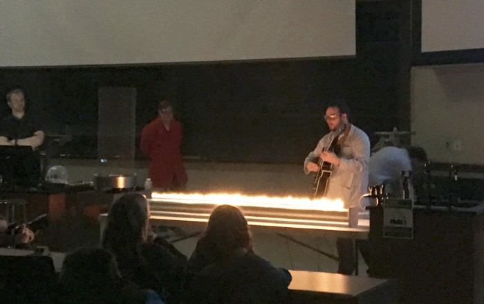 "Graduate student Craig Reingold performs an experiment using an electric guitar and fire during Tuesday's ""Our Universe Revealed"" lecture series installment, which engages audiences with science."