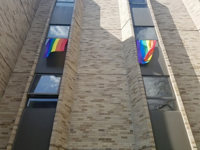LGBT flags hang out the windows of a residence hall as a protest against Vice President Pence's upcoming Commencement speech.